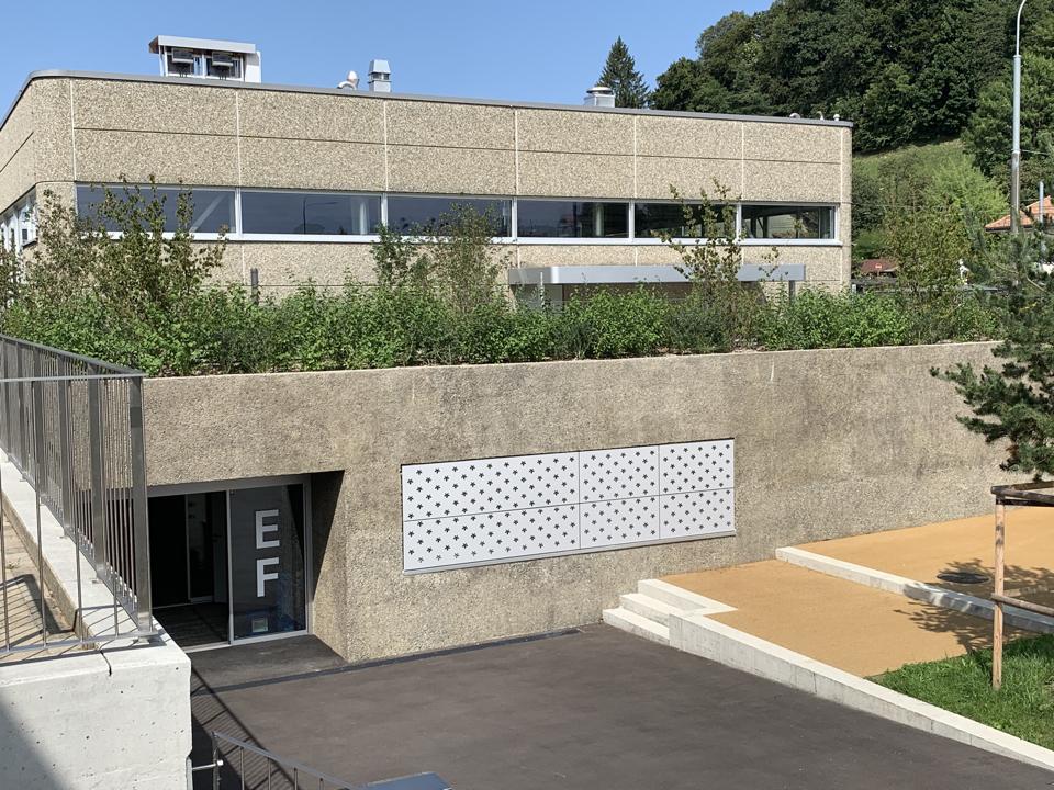 La matérialité de l'extension, un béton désactivé, fait écho au béton lavé des constructions existantes.