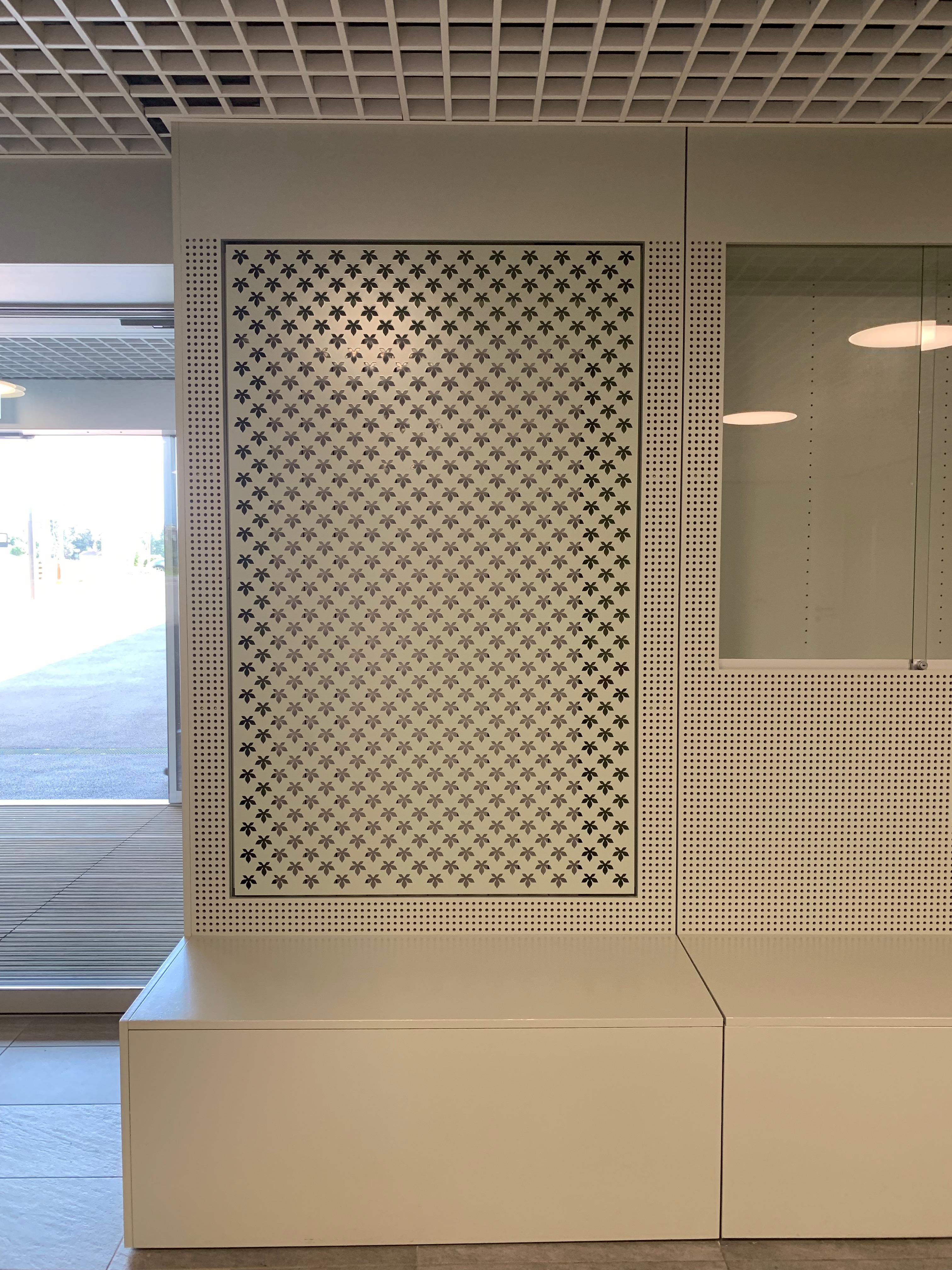 Hall d'accueil : détail du cache radiateur, du banc et d'une vitrine d'exposition.